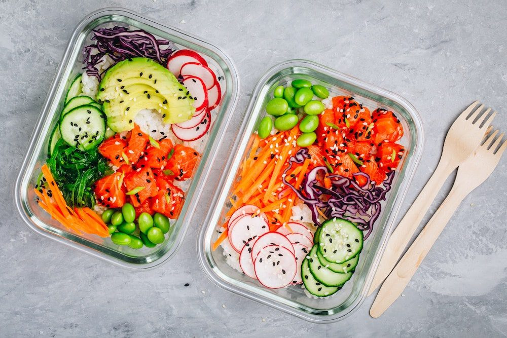 Poke meal prep containers with salmon, rice, radish, cucumber and avocado