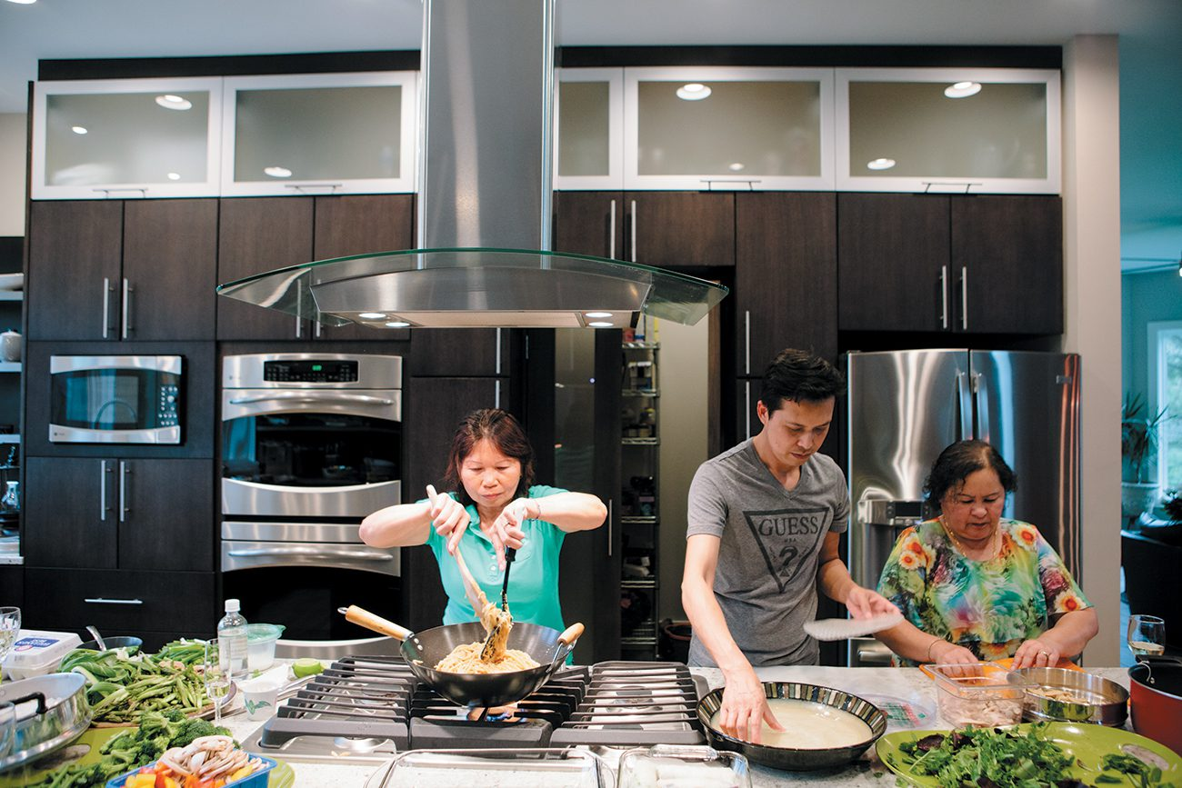 The Aylwards usually host a large open house on Easter, and this year, guests enjoyed a Thai feast. Ann's mother, Chuey Combs (left), cooks Thai noodles and stir-fry vegetables with tofu for 50 people while Ann's cousin Narong Kawsitte and family friend Rabiab Kaseth roll fresh spring rolls. Both Narong and Rabiab worked in Chuey's restaurant in Texas before she retired.