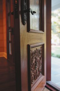 Solid Peruvian doors, set with swirling frosted glass and anchored by ornate detail, welcome the Salemsons into their home and the garage.
