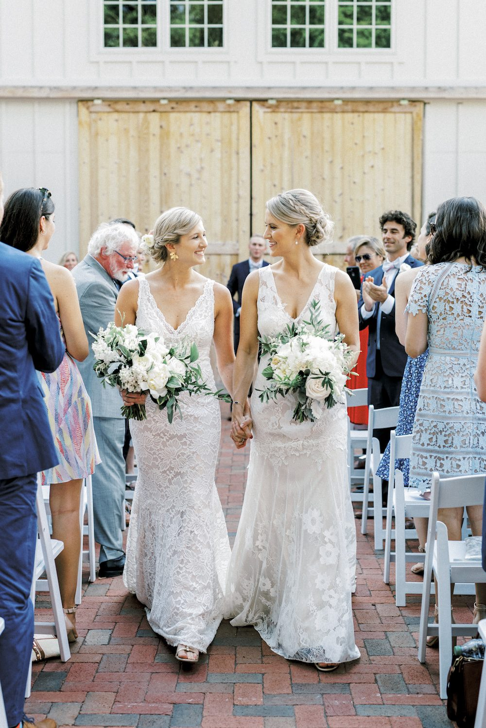 Paige and Kristine walk back down the aisle at The Barn of Chapel Hill at Wild Flora Farm as a married couple.