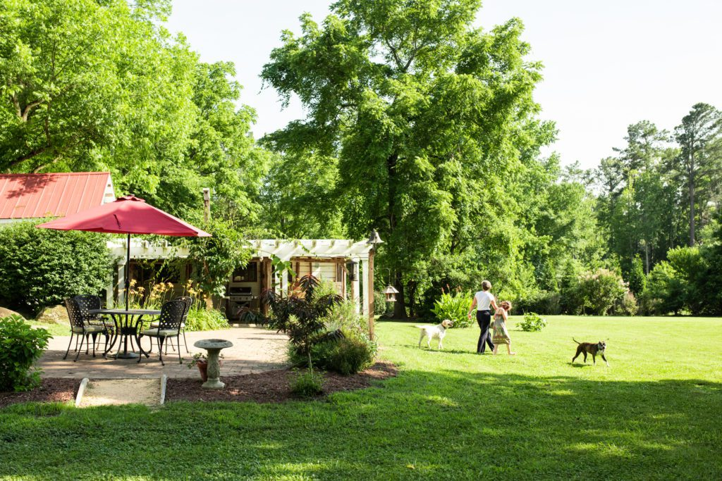 The Johnson family's outdoor seated area is surrounded by huge oak trees