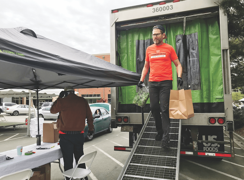 Acme's Kevin Callaghan unloads produce and a family meal from the truck.