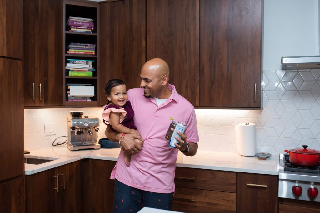 Custom-built home – A father holding his infant daughter in a kitchen