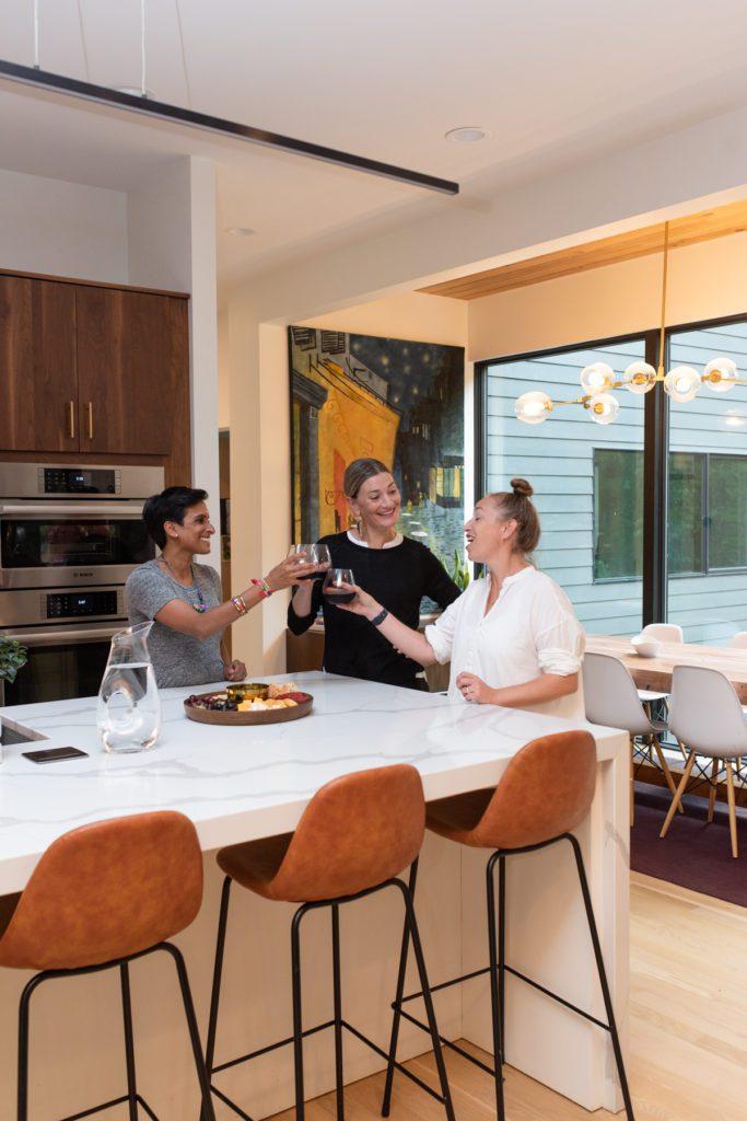 Custom-built home – Three women toast around a kitchen island