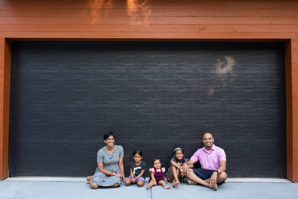 The Patel family sit in front of their custom-built home