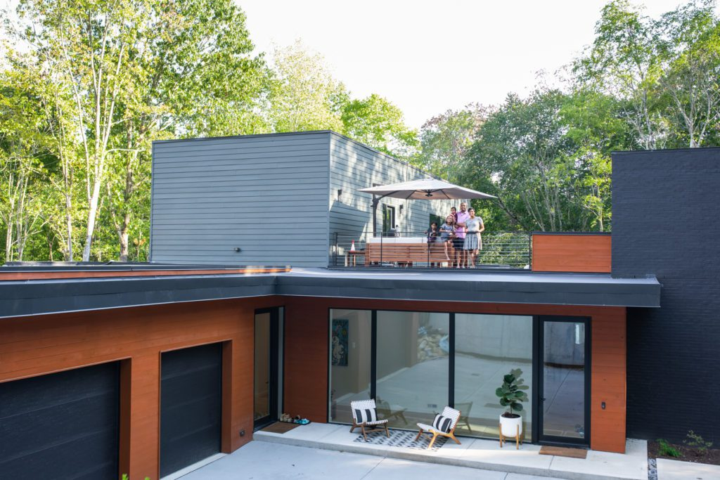 The Patel family stands on the roof of their custom-built home in Chapel Hill