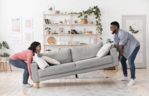 Couple moving a couch in their living room